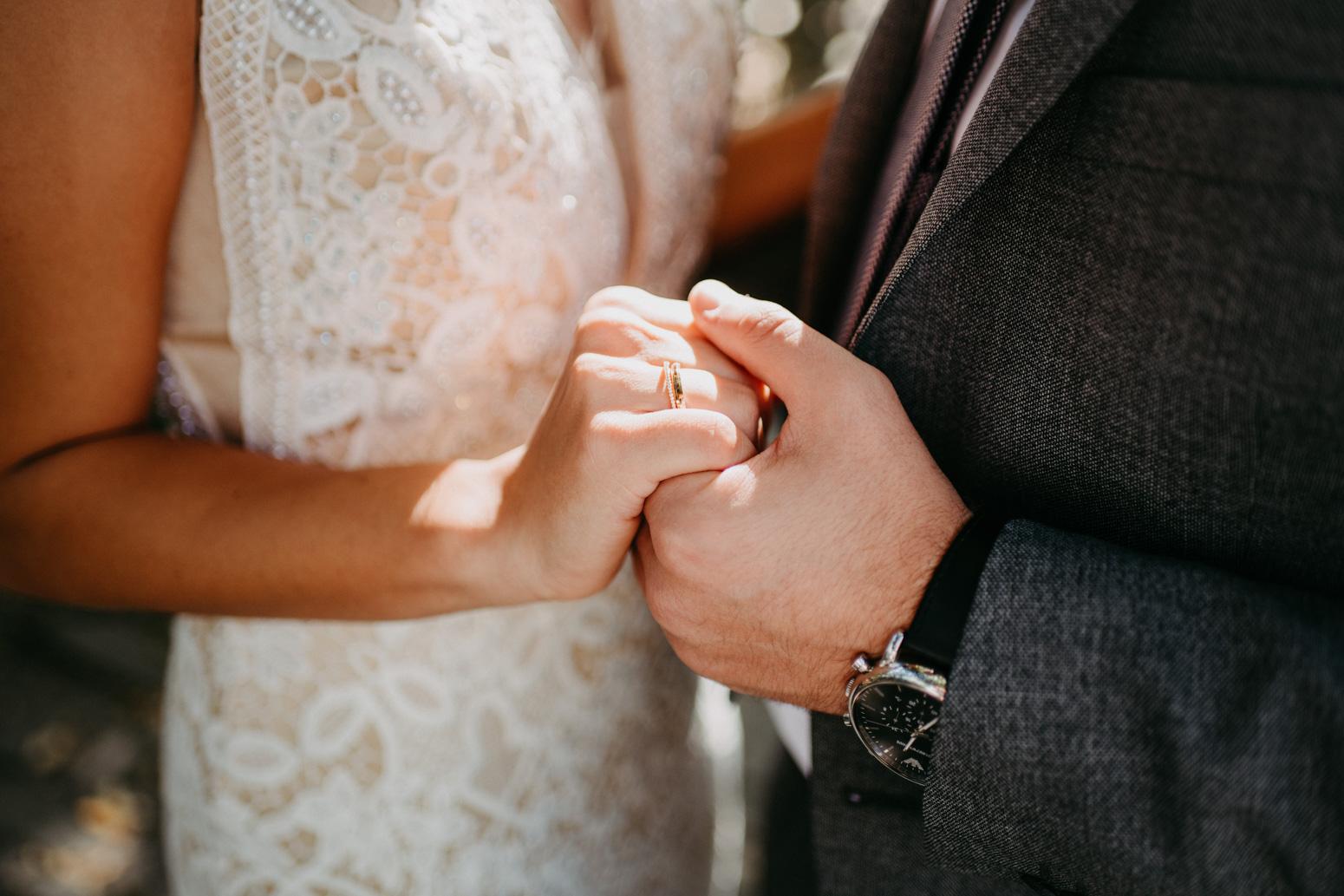 Bräutigam hält die Hand seiner braut, Brautpaarshooting am Schloss Broich in Mülheim an der Ruhr