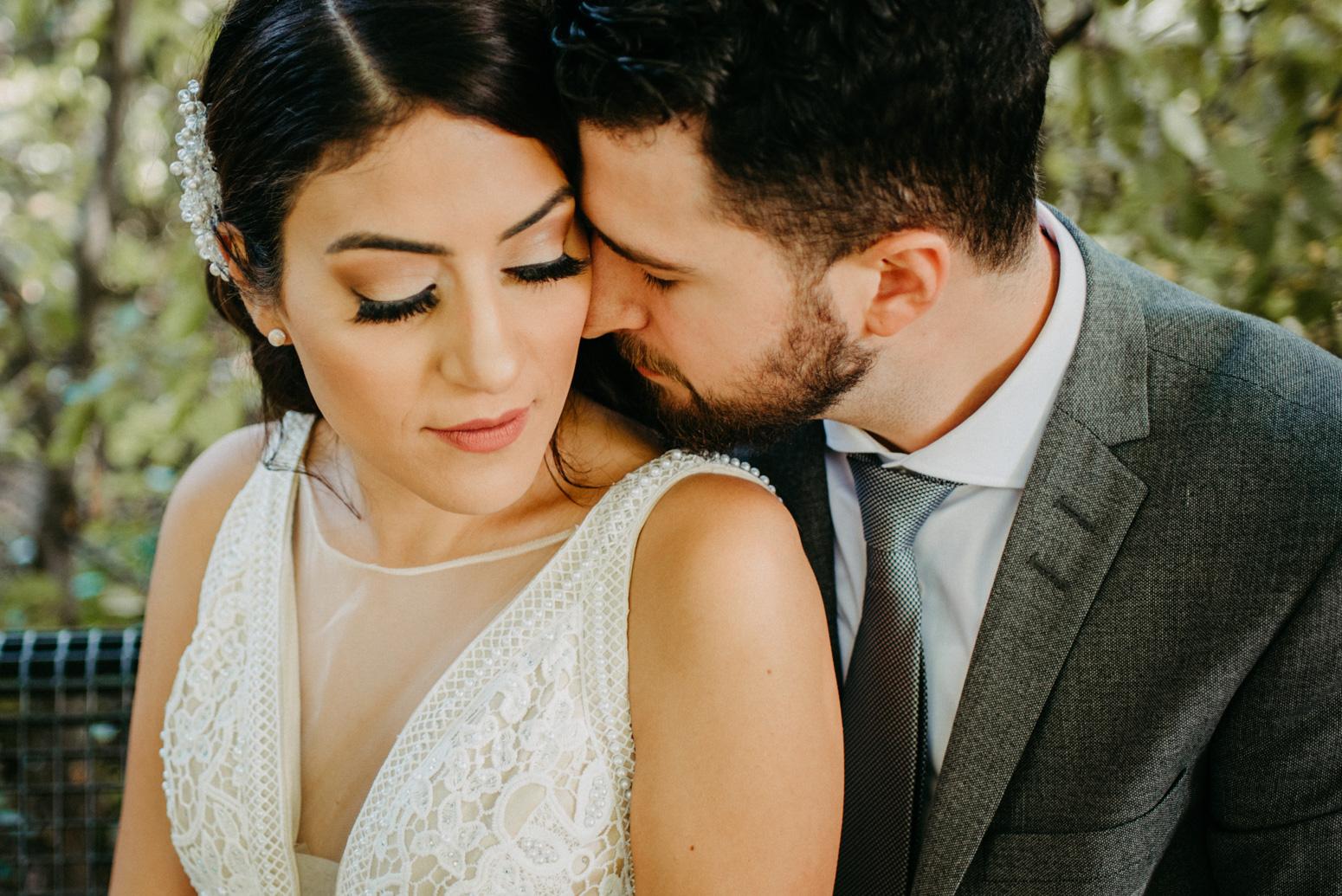 Bräutigam küsst den Hals seiner Frau beim Brautpaarshooting
